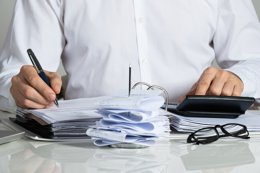 Midsection of businessman calculating invoice at office desk