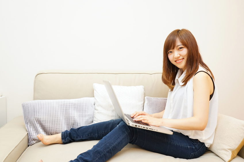 Young japanese woman using a computer on the sofa ソファーでリラックスしてパソコンを使う若い日本人の女性
