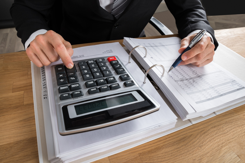 Close-up Of Male Accountant Calculating Tax At Desk In Office